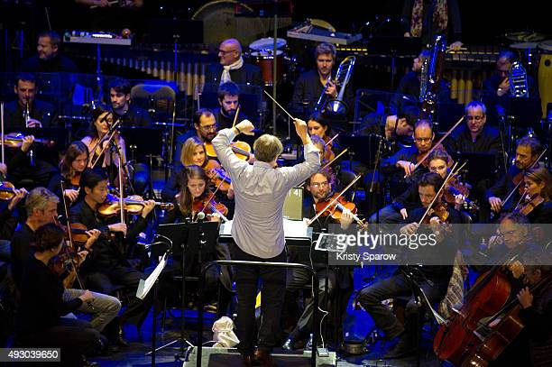 Conductor Ludwig Wicki leads his orchestra which includes the American composer Michael Giacchino during the 'Ratatouille Cine Concert' at Le Grand...