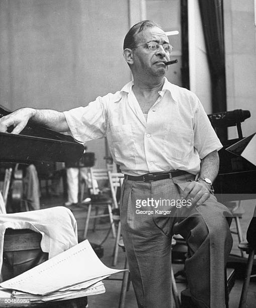 Conductor Max Steiner smoking a cigar while taking a break from conducting the New York Philharmonic orchestra during a rehearsal for singer Frank...