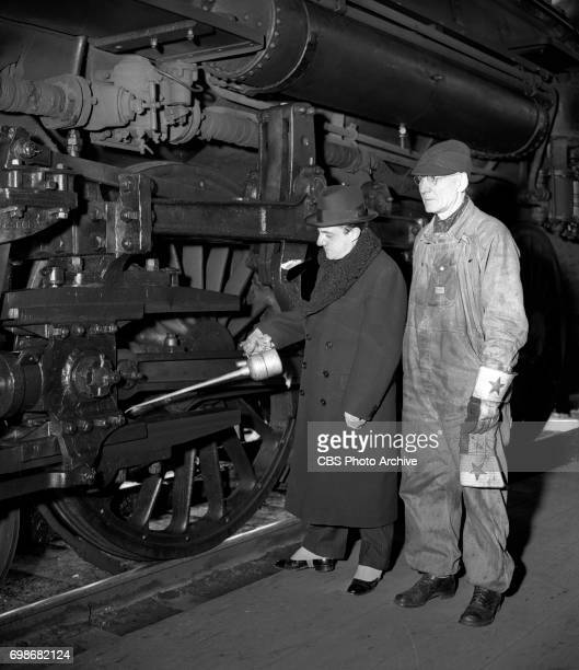 Conductor of the New York Philharmonic, John Barbirolli in Chicago, Illinois, oiling a train. Image dated November 26, 1939.