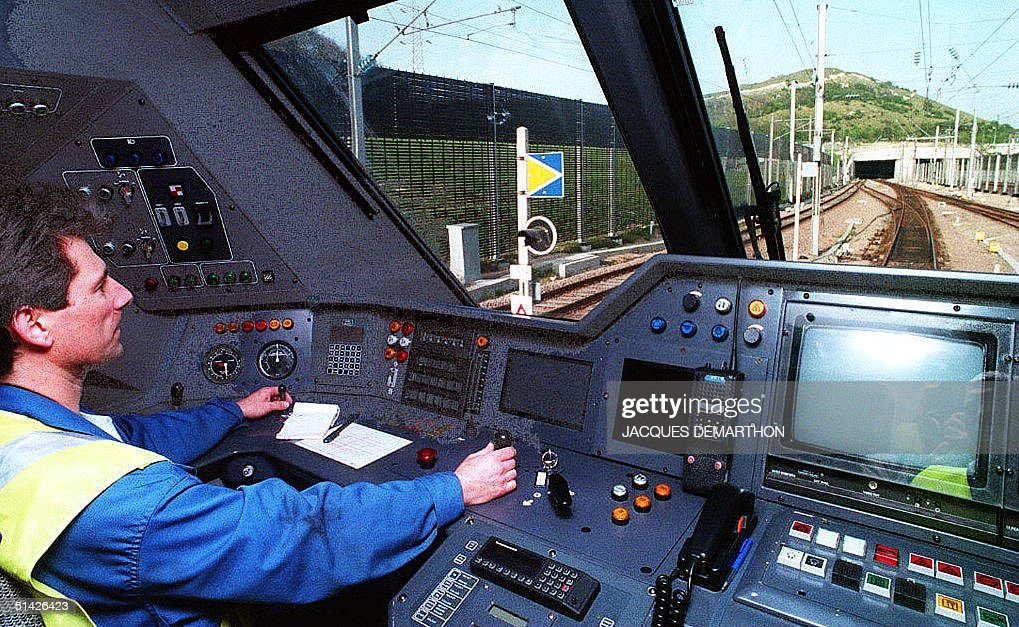 A conductor of the 'Trans-Manche' shuttle guides his train towards the entrance of the Chunnel (Channel tunnel, R) 02 May 1994 during a technical trial in Folkestone, UK. The Chunnel is due to be officially inaugurated by Queen Elizabeth II of England, and French President Francois Mitterrand 06 May.