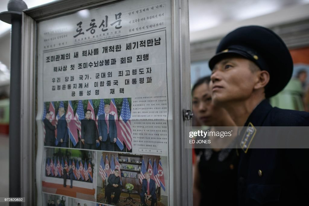 TOPSHOT - A conductor reads the latest edition of the Rodong Sinmun newspaper showing images of North Korean leader Kim Jong Un meeting with US president Donald Trump during their summit in Singapore, at a news stand on a subway platform of the Pyongyang metro on June 13, 2018. - Donald Trump accepted an invitation from Kim Jong Un to visit North Korea during their historic summit, Pyongyang state media reported on June 13, as the US president said the world had jumped back from the brink of 'nuclear catastrophe'.