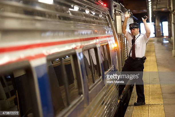 A conductor signals to a fellow conductor before departure as Amtrak resumes northbound service from 30th Street Station with a 553am departing train...