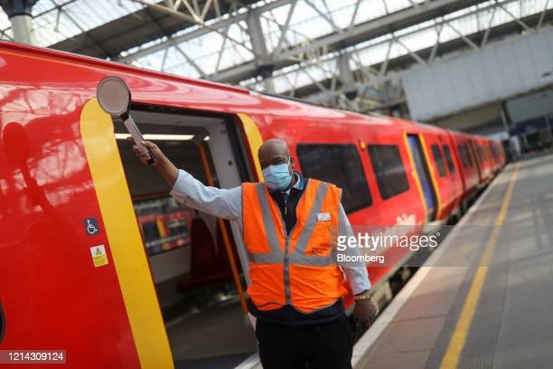 Conductor signals to a train driver from a platform at London Waterloo railway station in London, U.K., on Thursday, May 21, 2020. The government in...