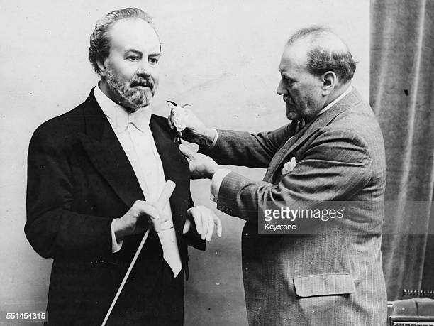 Conductor Sir Henry Wood inspecting a wax model in his likeness at Madame Tussauds London circa 1935