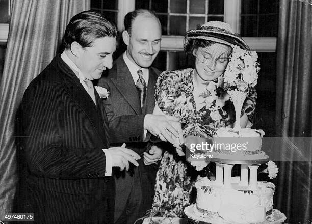 Conductor Sir John Barbirolli attending the wedding of harpist Rosemary St John and viola player George Alexander, cutting their wedding cake at...