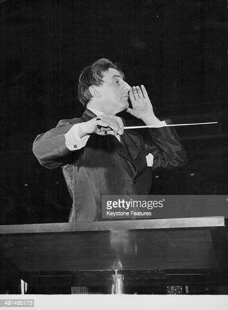 Conductor Sir John Barbirolli conducting on stage, circa 1955.