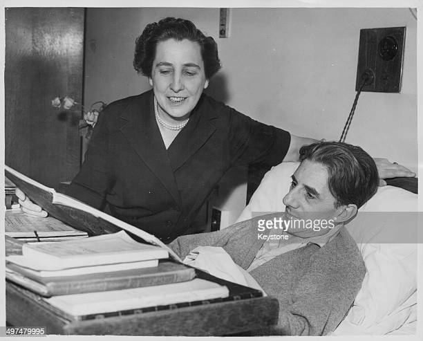 Conductor Sir John Barbirolli recuperating in hospital following an operation, as his wife reads to him in bed, September 6th 1956.