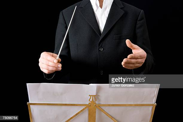 Conductor standing behind stand with sheet music
