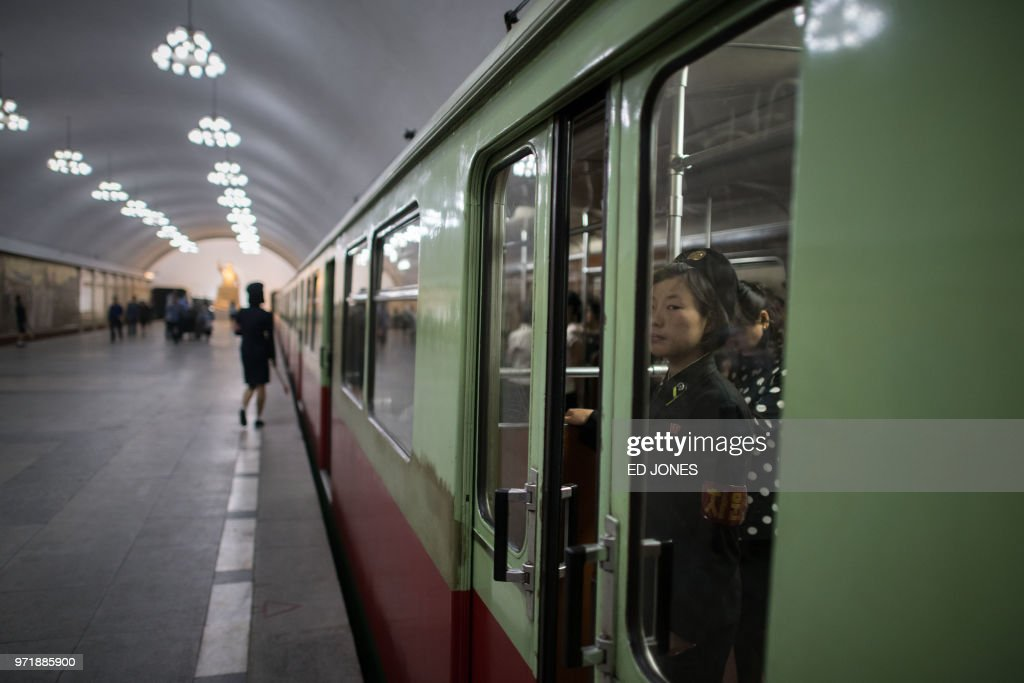 TOPSHOT - A conductor stands by the doors of a subway train of the Pyongyang metro on June 12, 2018. - Donald Trump and Kim Jong Un became on June 12 the first sitting US and North Korean leaders to meet, shake hands and negotiate to end a decades-old nuclear stand-off.