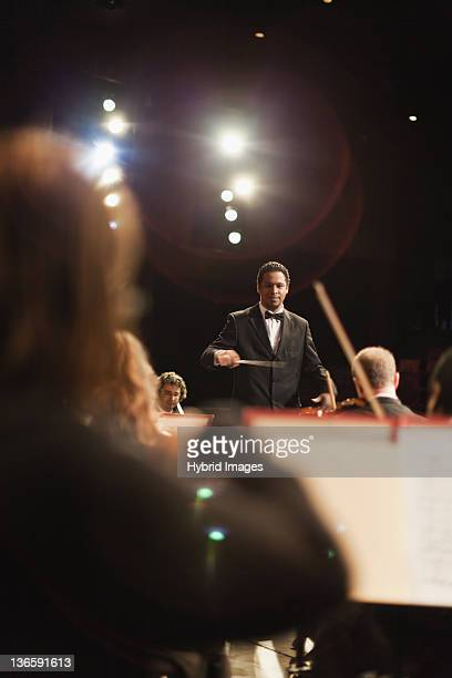 conductor waving baton over orchestra - maestro stock photos and pictures
