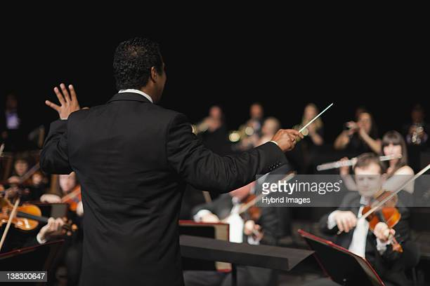 conductor waving baton over orchestra - orquestra - fotografias e filmes do acervo
