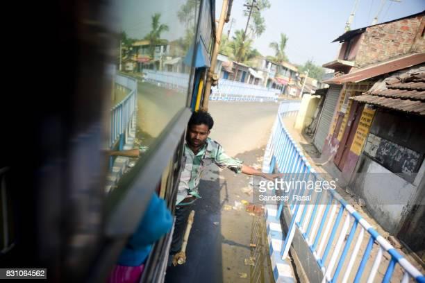 a conductor waving on running bus during ganga sagar fair - ganga sagar stock photos and pictures