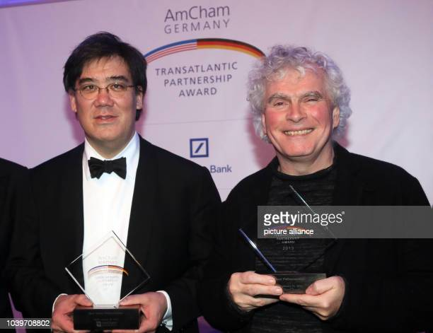 Conductors Alan Gilbert of the New York Philharmonic orchestra and Sir Simon Rattle of the Berlin Philharmonic orchestra talk to each other during...