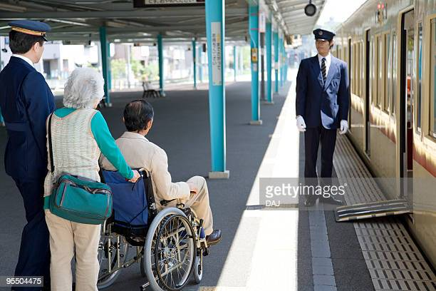 Conductors and senior couple at platform, senior man in wheelchair