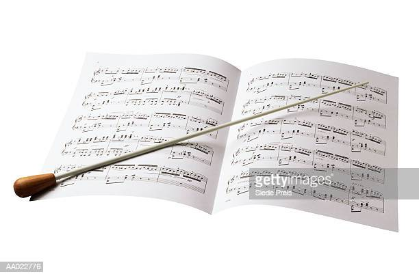 conductor's baton and sheet music - conductor's baton stock photos and pictures