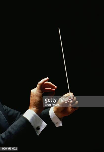 Conductor's hands holding baton, black background
