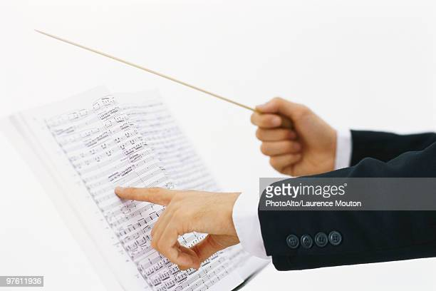 Conductor's hands with conductor's baton and musical score