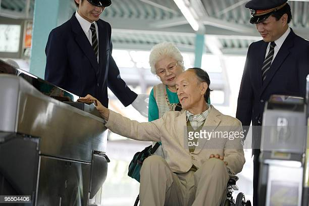 Conductors helping senior couple walking through turnstile at station, senior man in wheelchair