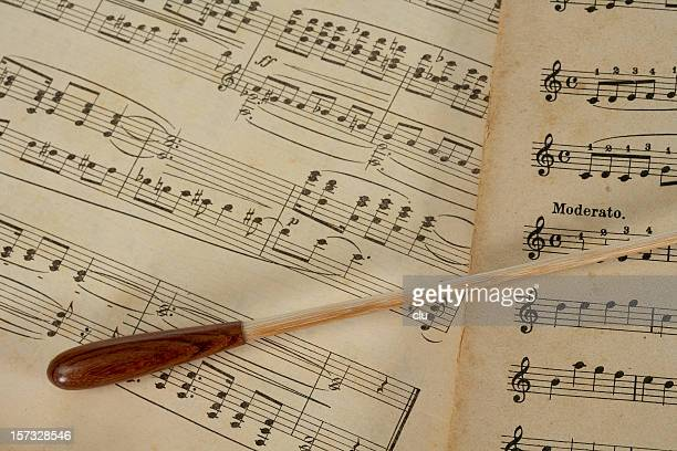 conductors's baton lying on music notes horizontal - conductor's baton stock photos and pictures