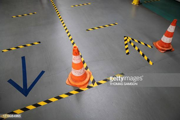 Cones and marks on the ground help employees of French automaker PSA Peugeot-Citroen to keep social distances required at Poissy's plant where are...