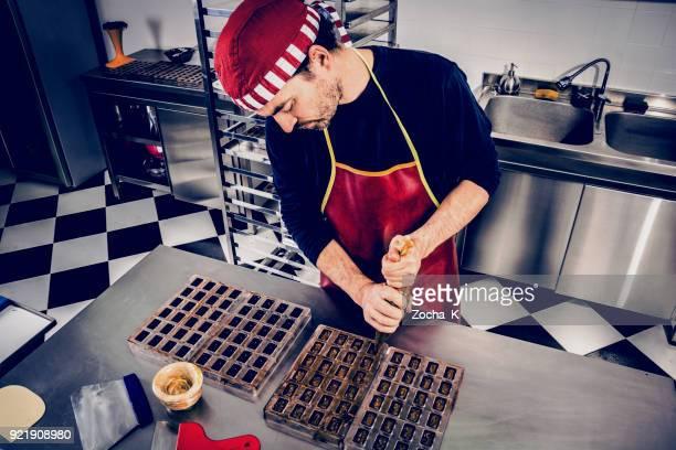 Confectioner makes chocolate pieces