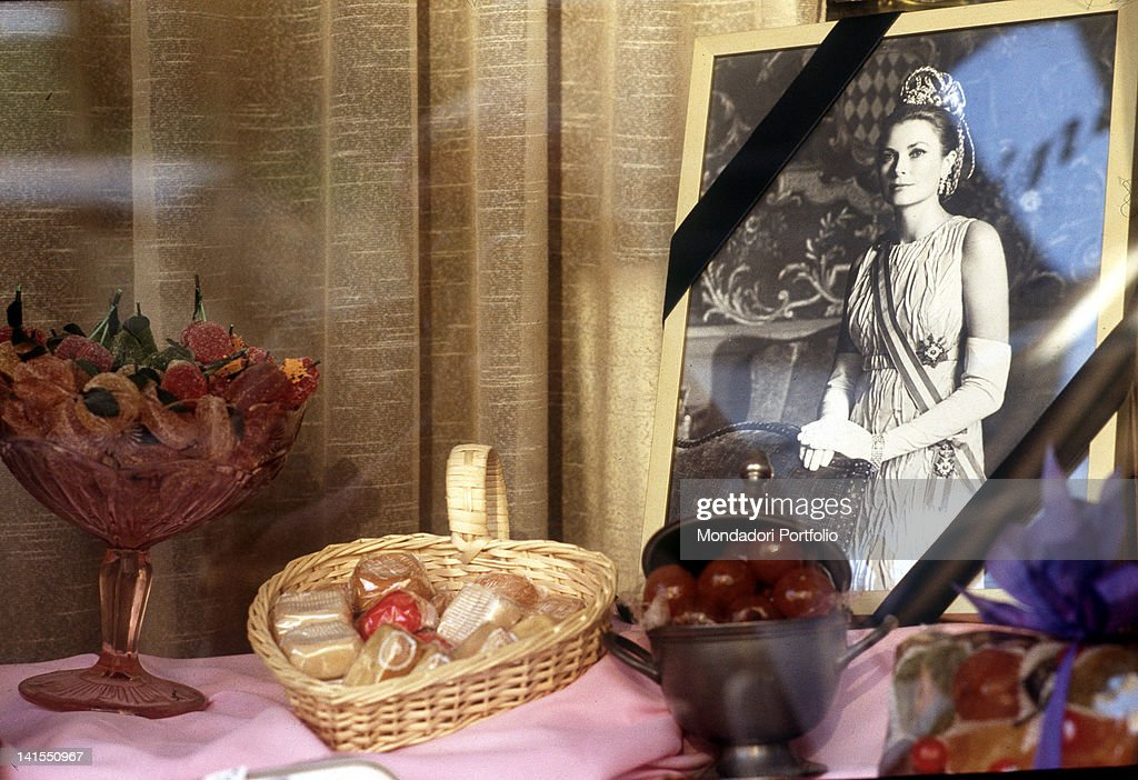 A confectioner shop's window displaying a draped in mourning photograph of Princess and American actress Grace Kelly, during her funeral. Monaco, September 1982