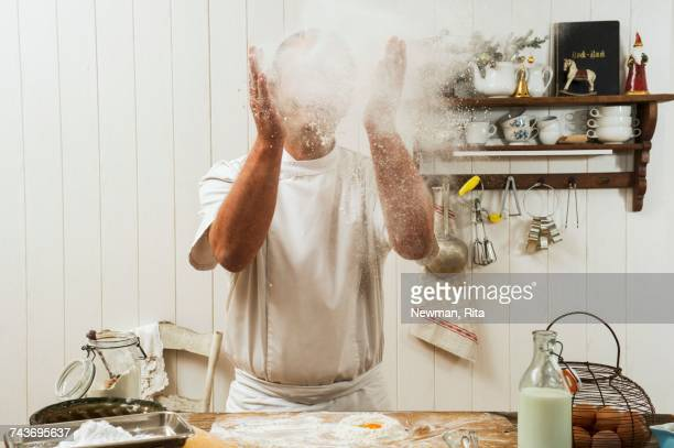 A confectioner sprinkling flour in the air