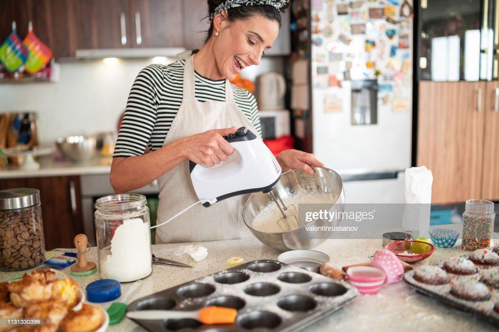 カップケーキのためのおいしいクリームを作る菓子女性 : ストックフォト