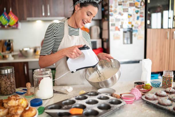 糖果師婦女為紙杯蛋糕製作美味的奶油 - 焗 預備食物 個照片及圖片檔