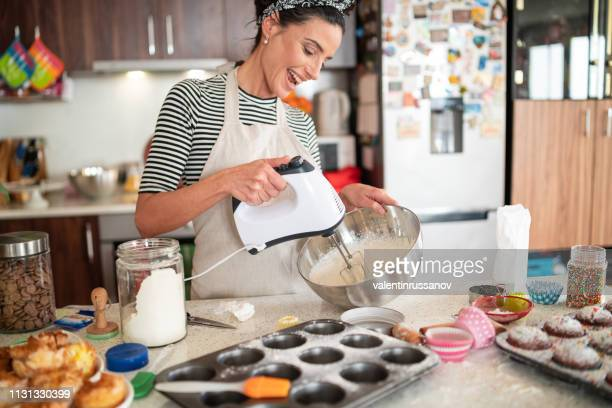 confectioner woman making delicious cream for cupcakes - sweet food stock pictures, royalty-free photos & images