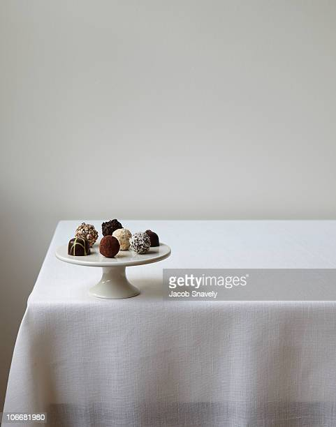 Confections displayed on white linen table.