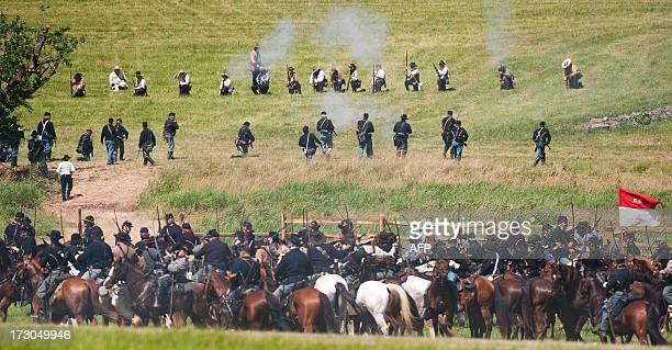 Confederate and Union Cavalry troops clash on the battlefield July 5 2013 at the 150th Gettysburg celebration and reenactments in Gettysburg...