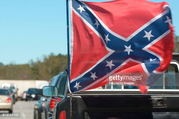 A confederate flag attached to the back of a pick up truck waves in the winds in Georgia