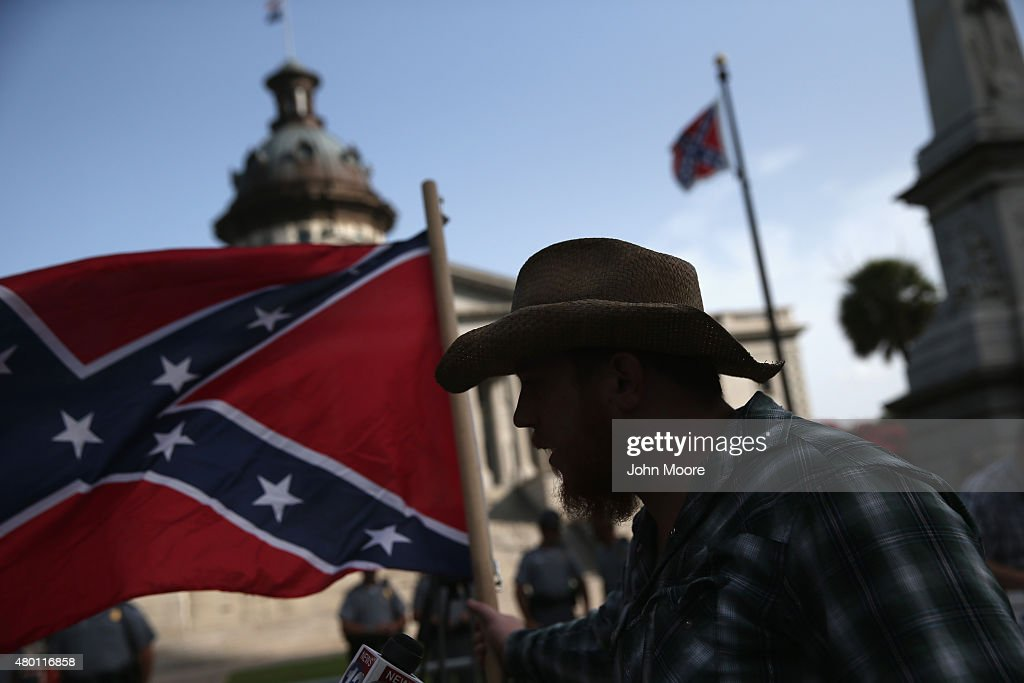 A Confederate flag supporter stands outside the South Carolina statehouse as the Confederate flag flies on July 9, 2015 in Columbia, South Carolina. South Carolina Governor Nikki Haley signed a bill to remove the Confederate flag from the statehouse grounds Friday morning.