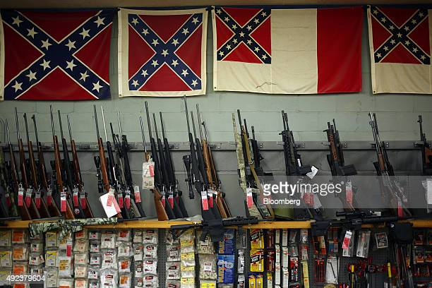 Confederate flags hang above various rifles that are displayed for sale during the Fall 2015 Knob Creek Machine Gun Shoot in West Point Kentucky US...