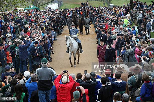 Confederate General Robert E Lee portrayed by American Civil War reenactor Thomas Lee Jessee rides through columns of Union troops and spectators...