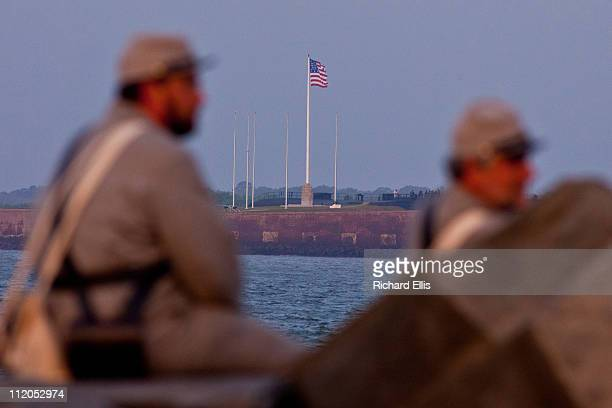 Confederate reenactors look out at Fort Sumter in Charleston Harbor from positions in Fort Moultrie early on April 12 2011 in Charleston South...