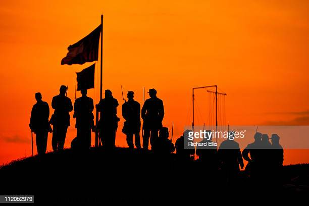 Confederate reenactors stand on the ramparts of Fort Moultrie are silhouetted in the rising sun to mark the 150th anniversary of the Civil War on...