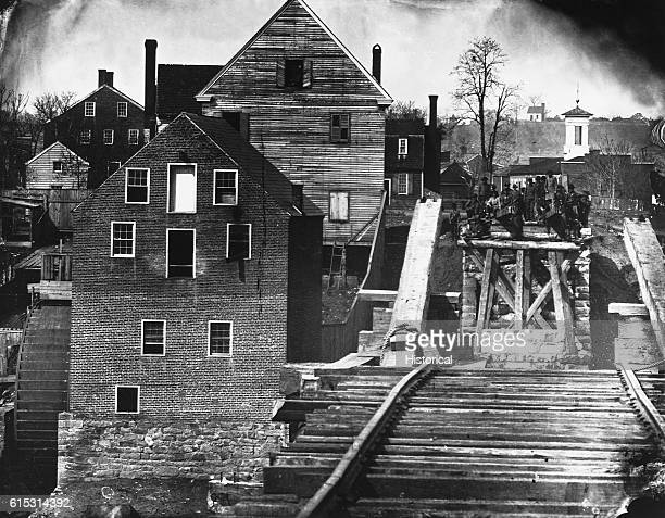 Confederate troops stand at the end of a bridge that has been destroyed in Fredericksburg Virginia site of the Battle of Fredericksburg in December...