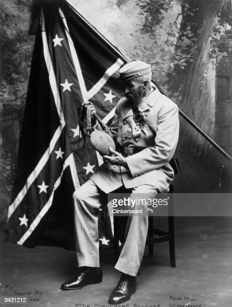 Confederate veteran with the Confederate flag behind him examining a Union water bottle