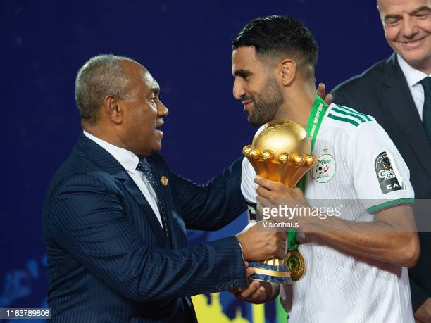 Confederation of African Football CAF President Ahmad Ahmad hands Riyad Mahrez of Algeria the trophy during the 2019 Africa Cup of Nations Final...