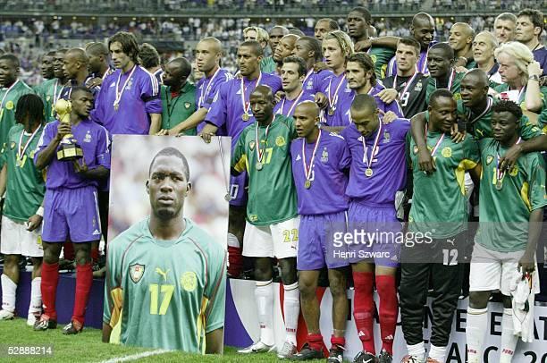 Confederations Cup 2003 Finale Paris Kamerun Frankreich 01 Spieler Frankreichs und Kameruns halten ein Foto von MarcVivien FOE/CMR der wenige Tage...