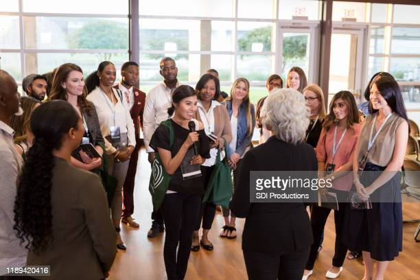 conference attendee asks question during conference - attending stock pictures, royalty-free photos & images