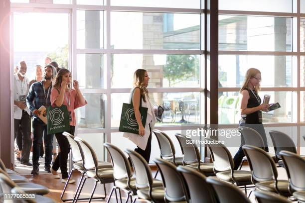 conference attendees file in for first day of events - attending stock pictures, royalty-free photos & images