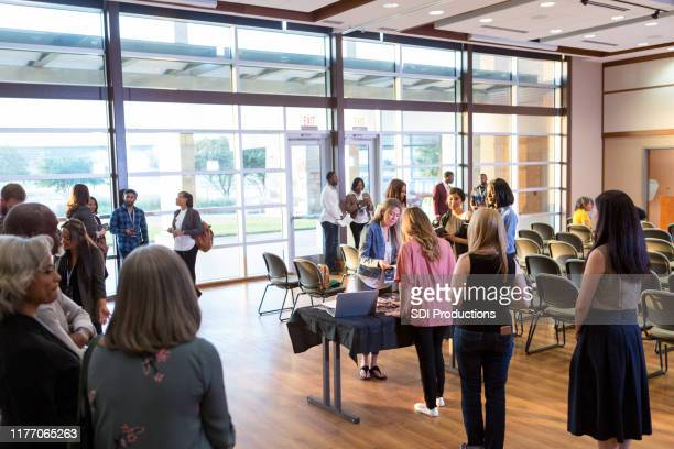 conference attendees stand in line to register - town hall stock pictures, royalty-free photos & images