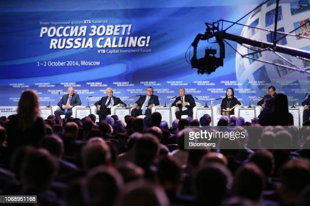 Conference delegates watch Vladimir Putin, Russia's president, on a large projection screen as he speaks on stage alongside Wanzhou Meng, chief...