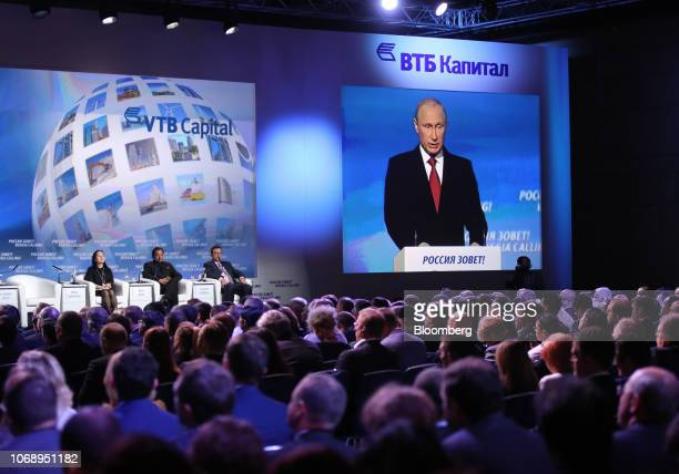 Conference delegates watch Vladimir Putin Russia's president on a large projection screen as he speaks on stage alongside Wanzhou Meng chief...