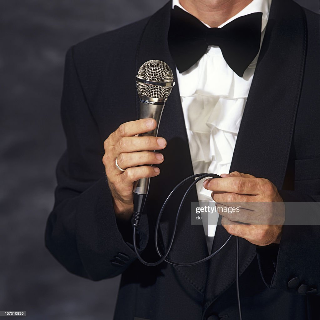Conferencier in elegant suit holding the microphone : Stock Photo