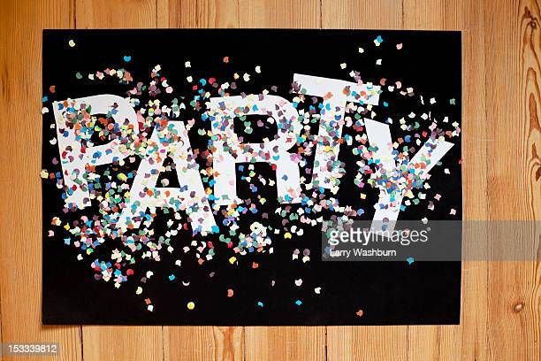 Confetti and letters spelling PARTY on a black poster board