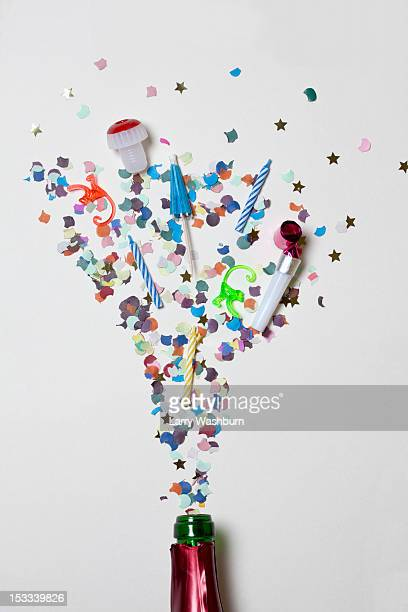 Confetti and party supplies spraying out of a champagne bottle